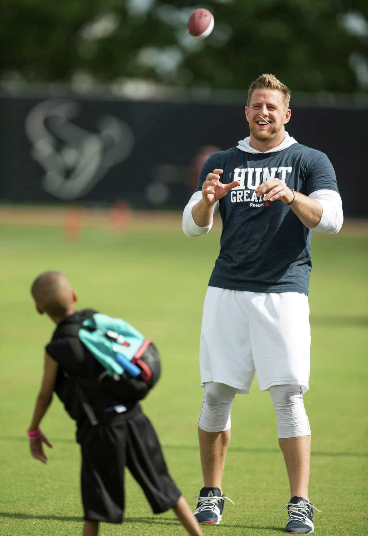 Houston Texans defensive end J.J. Watt plays catch with Jeston Adams during Texans training camp at Houston Methodist Training Center on Sunday, July 31, 2016, in Houston. Watt is unable to practice as he is recovering from back surgery.