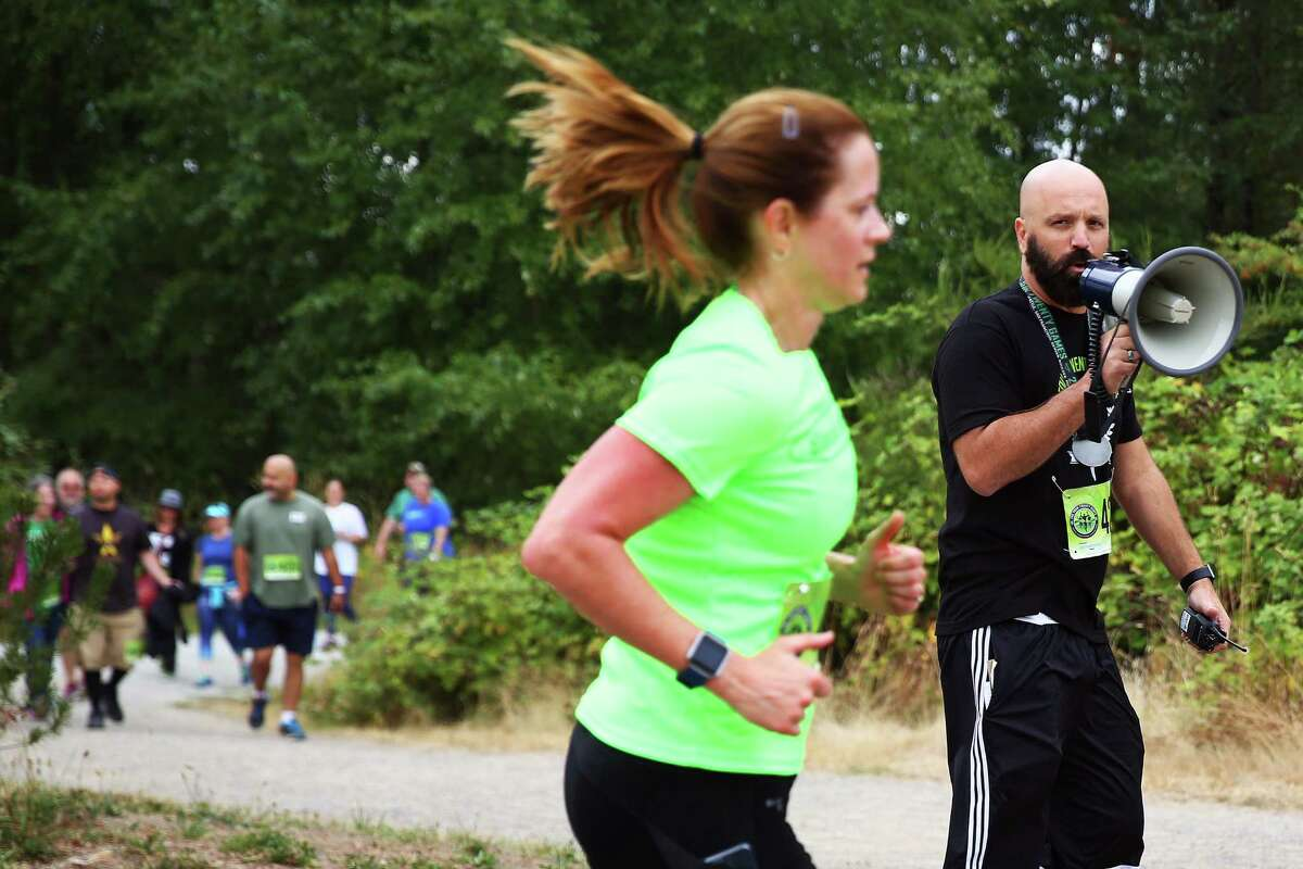 Event founder Jim McAlpine encourages Lorinda Hagstrom during the 4.20 mile race at the 420 Games, Sunday, July 31, 2016 at Magnuson Park. The 420 Games celebrate cannabis and physical fitness with events like the 4.20 mile run and a fitness challenge.