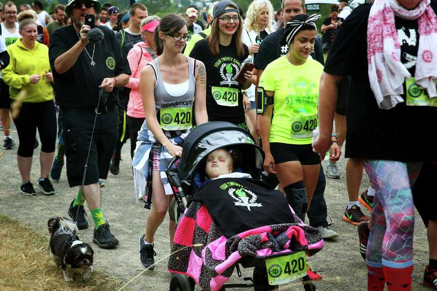 Meagan Holt pushes her three-year-old daughter Maddie in a stroller along the route of the 4.20 mile race at the 420 Games, Sunday, July 31, 2016 at Magnuson Park. Maddie Holt was diagnosed with a terminal genetic disorder called Zellweger Syndrome. Most children with this diagnosis do not live past one. After Maddie began having daily seizures, her parents took her to a host of doctors and tried many treatments, to no avail. Eventually, they found medical cannabis treatment to be the only helpful solution and Maddie went for nine months without seizing. She has been treated with CBD heavy cannabis oil for one-and-a-half years and is still seeing significant improvement. Her mother works with an organization called Project Positive Change that works to bring awareness to CBD treatment for medical issues.