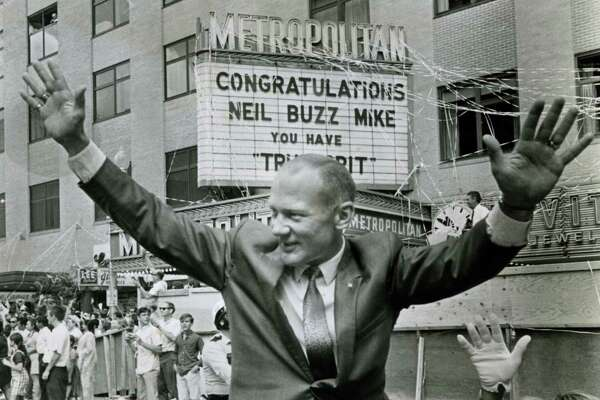 "08/16/1969 -- METROPOLITAN THEATER MARQUEE CONGRATULATES ASTRONAUTS - Apollo 11 astronaut Buzz Aldrin and wife by marquee telling moonmen they have ""True Grit"" during ticker tape parade in downtown Houston"