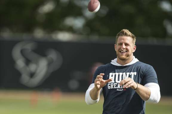 Houston Texans defensive end J.J. Watt plays catch with Jeston Adams during Texans training camp at Houston Methodist Training Center on Sunday, July 31, 2016, in Houston. Watt is unable to practice as he is recovering from back surgery. ( Brett Coomer / Houston Chronicle )