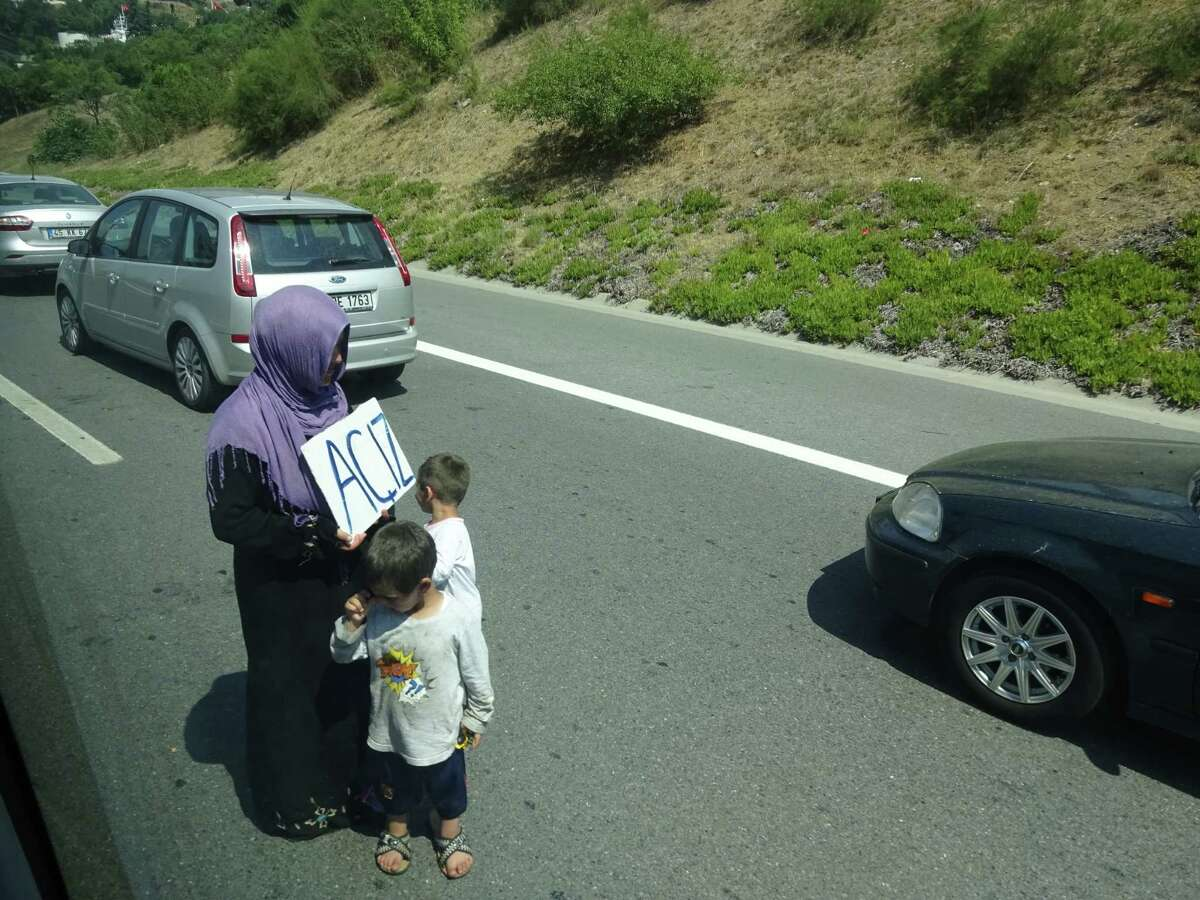 A Syrian refugee woman and her two young children beg for money on a highway in Istanbul during an afternoon traffic jam in the sprawling city of 16 million (Paul Grondahl / Times Union)