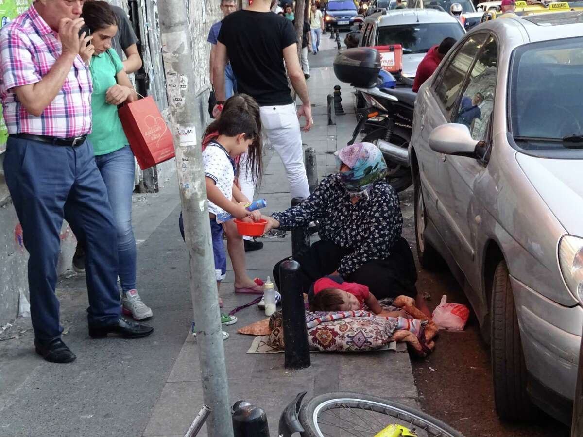 A Syrian refugee woman and her children beg from passersby near Taksim Square in Istanbul (Paul Grondahl / Times Union)
