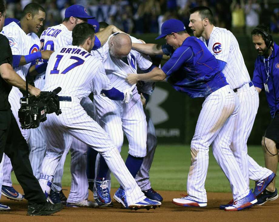 Chicago Cubs players rip the jersey off of Jon Lester, center, after he hit a game winning sacrifice bunt which scored Jason Heyward in the twelfth inning of a baseball game against the Seattle Mariners on Sunday, July 31, 2016, in Chicago. The Chicago Cubs beat the Seattle Mariners 7-6. (AP Photo/Matt Marton) Photo: Matt Marton, Associated Press / FR170980 AP
