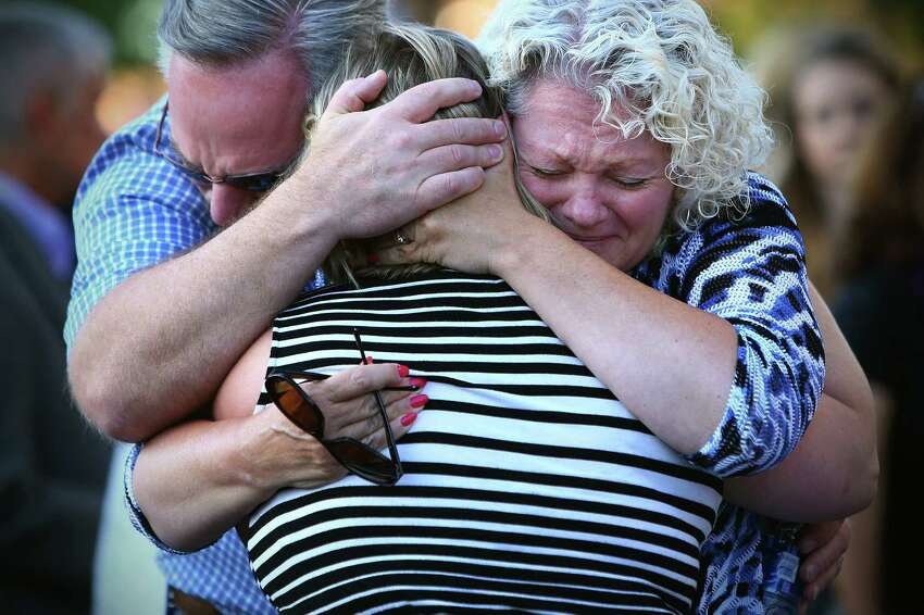 The mother of shooting victim Jake Long, center, is embraced during a community vigil honoring the victims of a shooting that occurred early Saturday morning at a house in Mukilteo, killing three teenagers and injuring one, Sunday, July 31, 2016 at the Mukilteo Church of Jesus Christ of the Latter Day Saints.