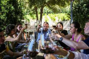A group clinked their wine glasses as they ate lunch and drank wine, during a tasting at Hopper Creek winery in Napa, California, on Friday, July 29, 2016.