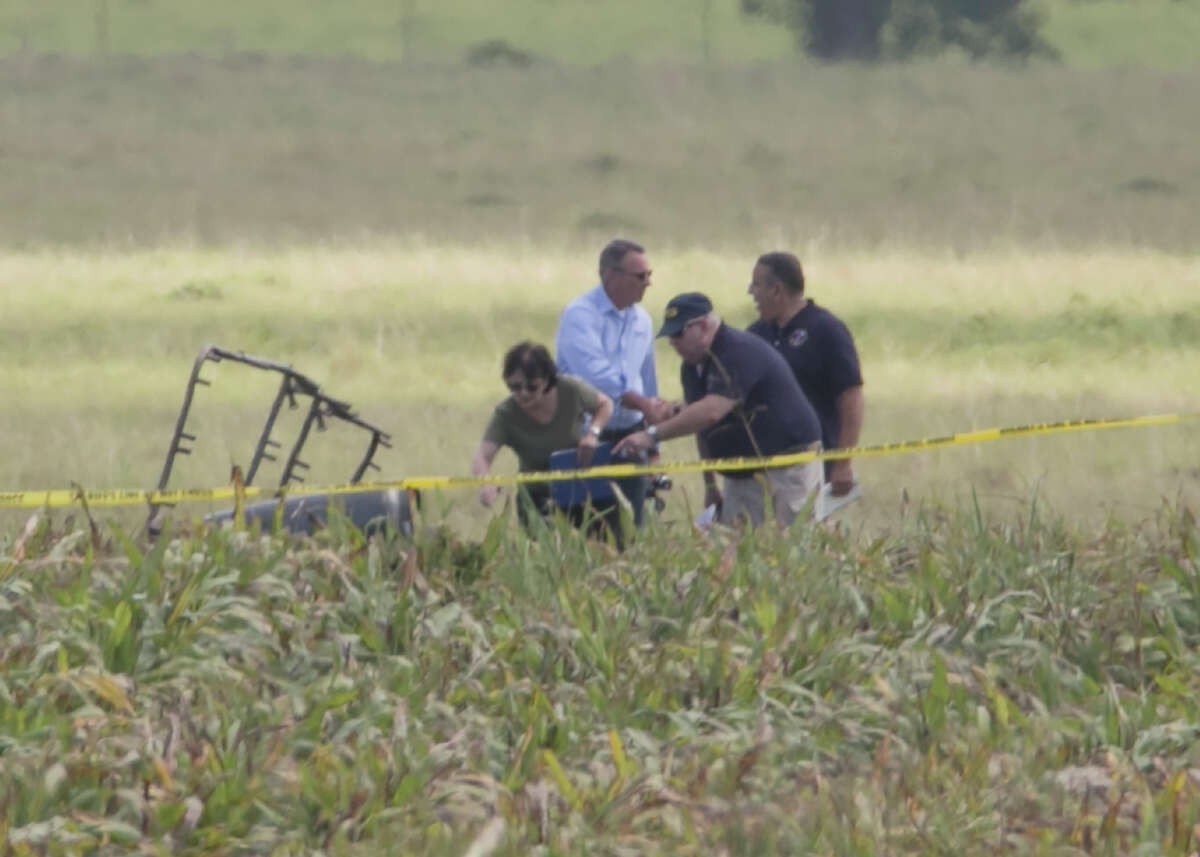 1. The hot air balloon launched around 7 a.m. Saturday from Fentress Texas Airpark, traveled about eight miles and crashed near Lockhart after striking a power line, killing all 16 on board. The partial frame of a hot air balloon is visible above a crop field as investigators comb the wreckage of a crash Saturday, July 30, 2016, in Central Texas near Lockhart, Texas. (Ralph Barrera/Austin American-Statesman via AP)