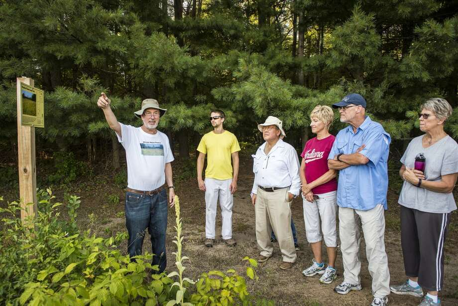 "Jim McLean leads a group through a the Meadow Flower Loop Trail during a program at the McLean Nature Preserve in northern Bay County on Tuesday. The McLean Nature Preserve, owned by Jim and Shirley McLean of Midland, covers 120 acres of land. About 15 people attended the program to hear Jim McLean explain how they established large plots of wildflowers, which is particularly helpful to pollinators, such as bees and butterflies. The plots, which range from a few square feet to one acre, include coneflowers, false sunflowers, bee balm, lupine, cosmos, Queen Anne's lace and blanket flowers, among others.  ""Some wildflowers are what others call weeds. I guess it's in the eye of the beholder,"" McLean joked. ""The purpose of this project is to benefit pollinators,"" McLean said. Photo: Danielle McGrew Tenbusch/for The Daily News"
