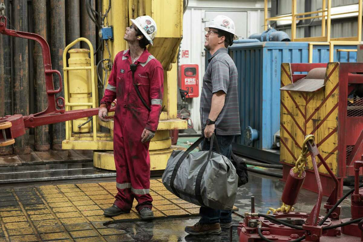 """Dylan O'Brien, left, plays crew member Caleb Holloway in """"Deepwater Horizon."""" Mark Wahlberg, right, stars as Mike Williams. Both survived the rig explosion that killed 11 of their colleagues."""