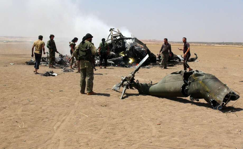 Rebels gather at the wreckage of a Russian Mi-8 helicopter after it was shot down in Syria's Idlib province. The copter had been delivering humanitarian supplies to the city of Aleppo. Photo: MOHAMED AL-BAKOUR, AFP/Getty Images