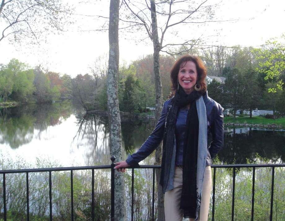 Taylor Gibson-Ullman poses in her backyard before a view of New Canaan's Collins Pond. Photo: Brittany Lyte / New Canaan News