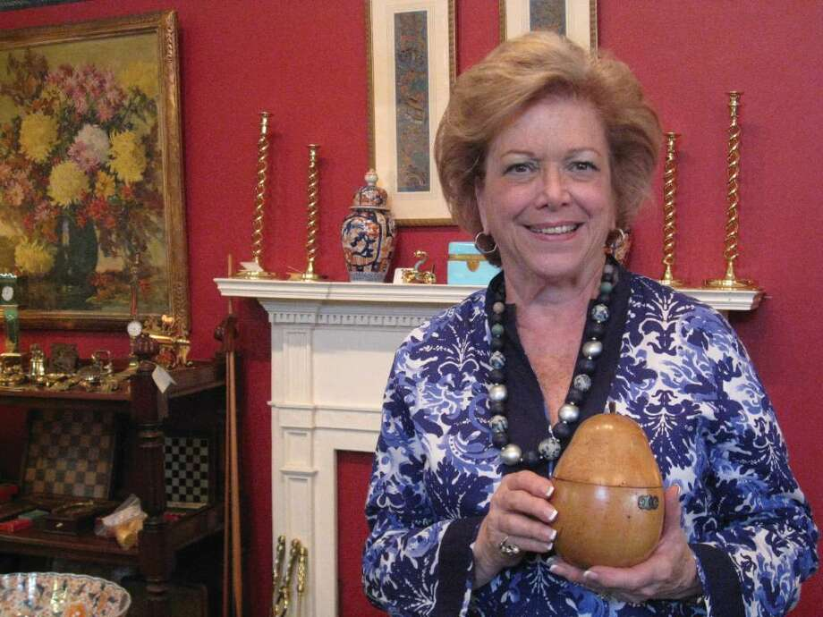 Sally B. Kaltman, owner of Sallea Antiques on Elm Street in New Canaan, stands in her shop holding an English pear-shaped tea caddie made of polished fruitwood circa 1780 to 1800. Photo: Brittany Lyte / New Canaan News