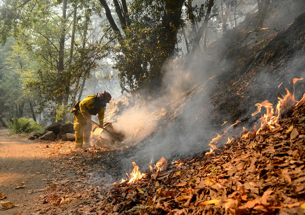 Rancho Adobe Fire Captain James Devrloo keeps an eye on a fire line on Garza Trail in the Rancho San Carlos Community as the Soberanes Fire burns in Carmel Valley, Calif., Wednesday, July 27, 2016.