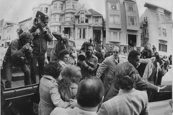 Patricia Hearst who was kidnaped, and participated in crimes of the SLA  Is shown here walking on her way out of the Golden Gate Avenue house, where she was kept prisoner  during her bank robbery trial February 15, 1976, Accompaning her are U.S. Marshalls and the press  Photo ran 02/22/1976, p. 5 (This World)