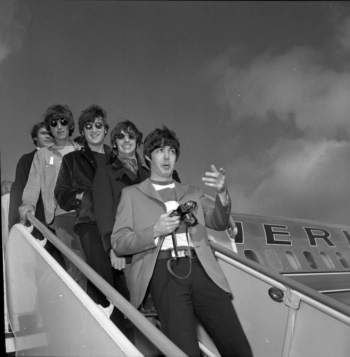 The Beatles arrive in San Francisco on August 29, 1966 for their concert at Candlestick Park. Paul McCartney, Ringo Starr, John Lennon and George Harrison are shown walking down the stairs from an airplane.