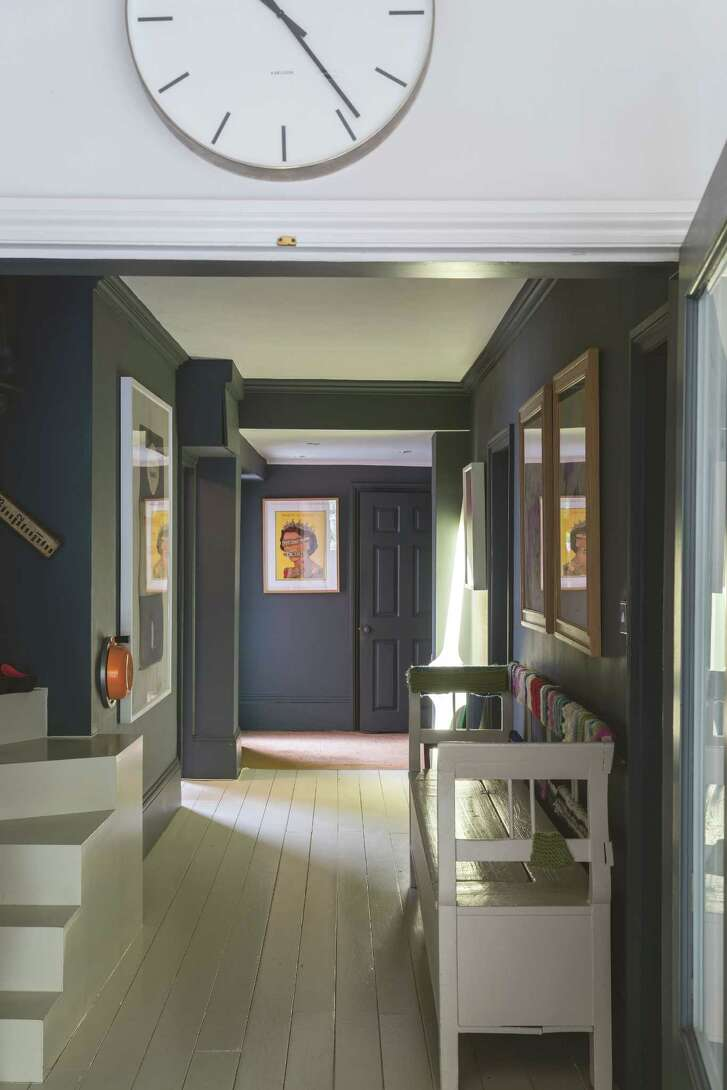 The hallway in Joa Studholme's home has dark gray walls. Its white floors reflect light onto the walls to brighten what otherwise could be a too-dark space.