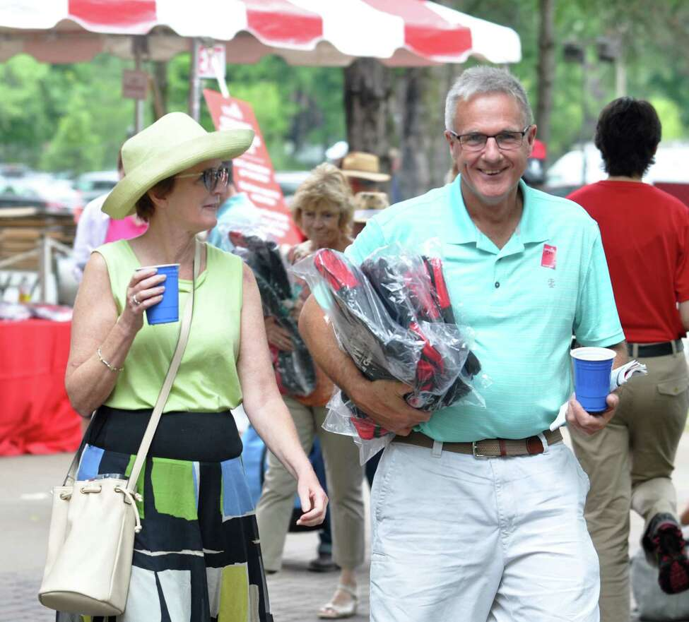 Stephanie, left, and John Devins, right, after collecting their Saratoga duffle bag during the giveaway at the racetrack on Monday, Aug. 1, 2016 in Saratoga Springs, N.Y. (Eliza Mineaux/Special to the Times Union)