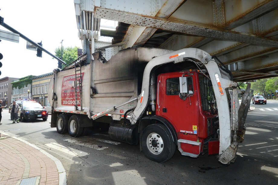 A garbage truck operated by Independent Refuse Service failed to clear the Metro-North Rairoad bridge over South Main and Washington streets in SoNo Monday afternoon. Several feet of the garbage truck's roof was sheared off and firmly wedged under the railroad bridge. The unidentified driver was cited by police. Photo: Alex Von Kleydorff / Hearst Connecticut Media / Connecticut Post