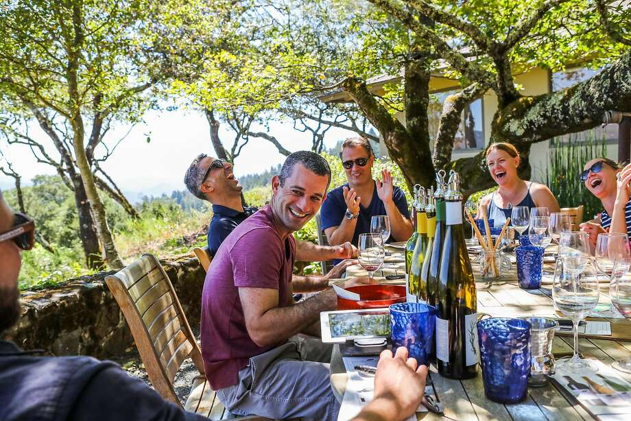 A group of visitors from New Jersey laugh as they listen to a joke told by Alex McCrea (left), as he leads a wine tasting at Stony Hill winery in Napa. Photo: Gabrielle Lurie, Special To The Chronicle