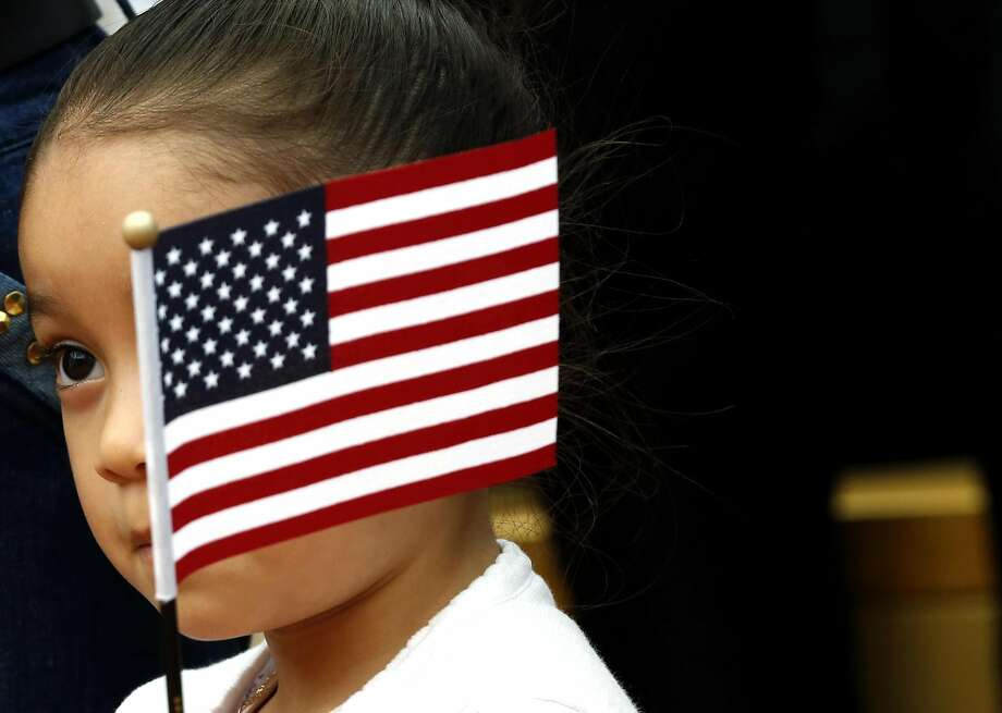 Alma Cecilia Rubalcaba, 4, waves an American flag in front of her face during a naturalization ceremony at Children's Fairyland in Oakland, California, on Monday, August 1, 2016. Photo: Connor Radnovich, The Chronicle