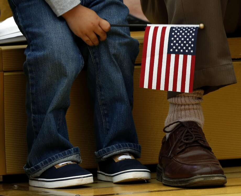 A child holds an American flag while sitting beside his father during a naturalization ceremony at Children's Fairyland in Oakland on Aug. 1. Photo: Connor Radnovich, The Chronicle
