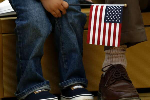 A child holds an American flag while sitting beside his father during a naturalization ceremony at Children's Fairyland in Oakland, California, on Monday, August 1, 2016.