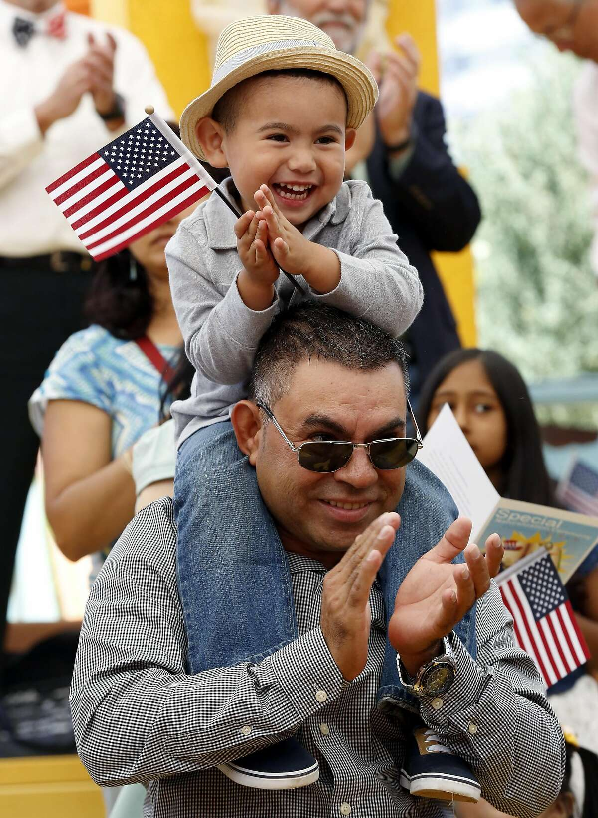 Wilber Quintanilla Jr., 3, sits on his father's shoulders during a naturalization ceremony at Children's Fairyland in Oakland, California, on Monday, August 1, 2016.