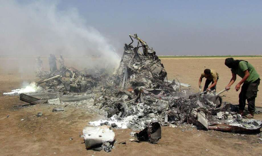 Syrian rebels inspect the wreckage of a Russian Mi-8 military transport helicopter after it was shot down in the Syrian province of Idlib, killing the three crew members and two officers aboard, according to Russian officials. Photo: MOHAMED AL-BAKOUR, Stringer / AFP or licensors