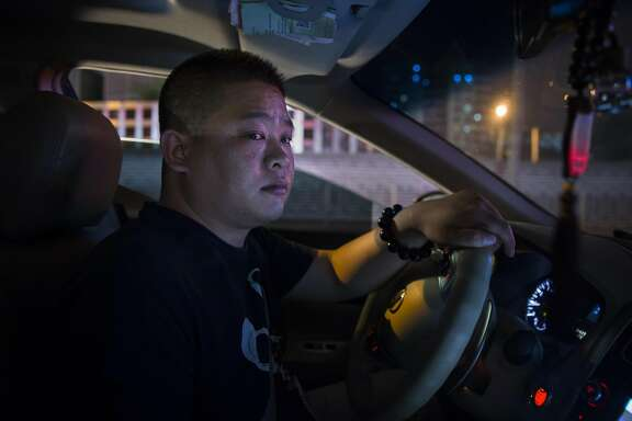 FILE-- An Uber driver in Beijing, May  28, 2015. In a new law announced on July 28, 2016, by several regulators, China�s government gave the thumbs-up for ride-hailing companies like Uber and its Chinese rival, Didi Chuxing, to operate in the country. The law clears up regulatory uncertainty and lays out a new framework under which ride-hailing companies can operate in the country. (Adam Dean/The New York Times)