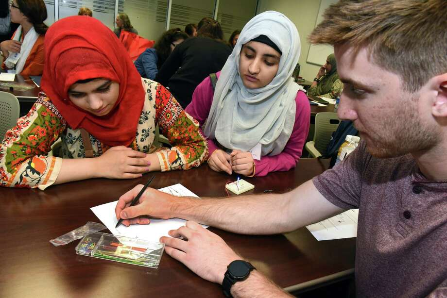 Graduate student Kasey Hogan, right, helps Pakistan girls Aamna Badar, 16, left, and Asma, 17, learn about sustainable energy by building LEDs at the State University of New York Polytechnic Institute on Monday, Aug. 1, 2016 in Albany, N.Y. The Pakistan girls sent to the US are visiting the Girls Inc. summer camp at SUNY Poly.(Lori Van Buren / Times Union) Photo: Lori Van Buren / 20037510A