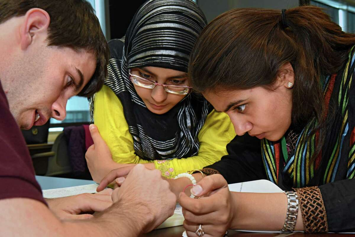 Undergraduate student Sean Tozier, left, helps Pakistan girls Aneela Bibi,17, center, and Kainat Batool, 17, learn about sustainable energy building LEDs at the State University of New York Polytechnic Institute on Monday, Aug. 1, 2016 in Albany, N.Y. The Pakistan girls sent to the US are visiting the Girls Inc. summer camp at SUNY Poly.(Lori Van Buren / Times Union)