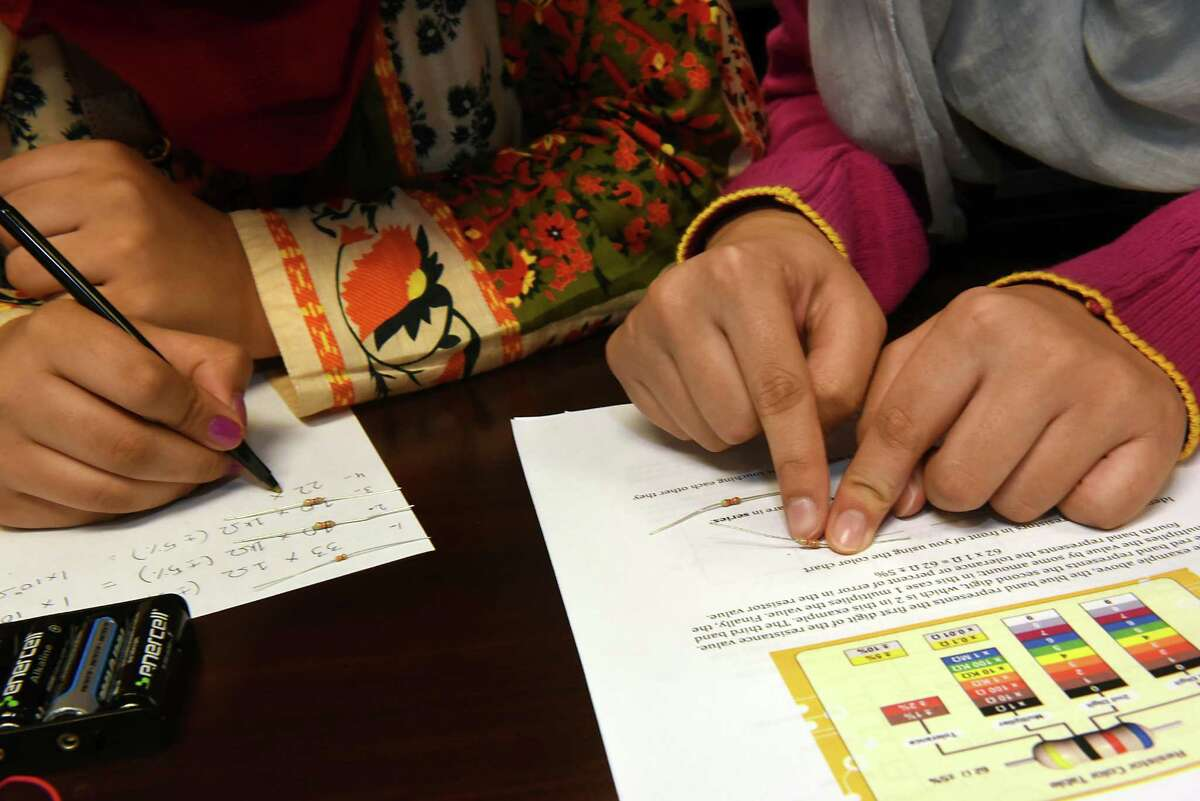 Pakistan girls Aamna Badar, 16, left, and Asma, 17, learn about sustainable energy building LEDs at the State University of New York Polytechnic Institute on Monday, Aug. 1, 2016 in Albany, N.Y. The Pakistan girls sent to the US are visiting the Girls Inc. summer camp at SUNY Poly.(Lori Van Buren / Times Union)