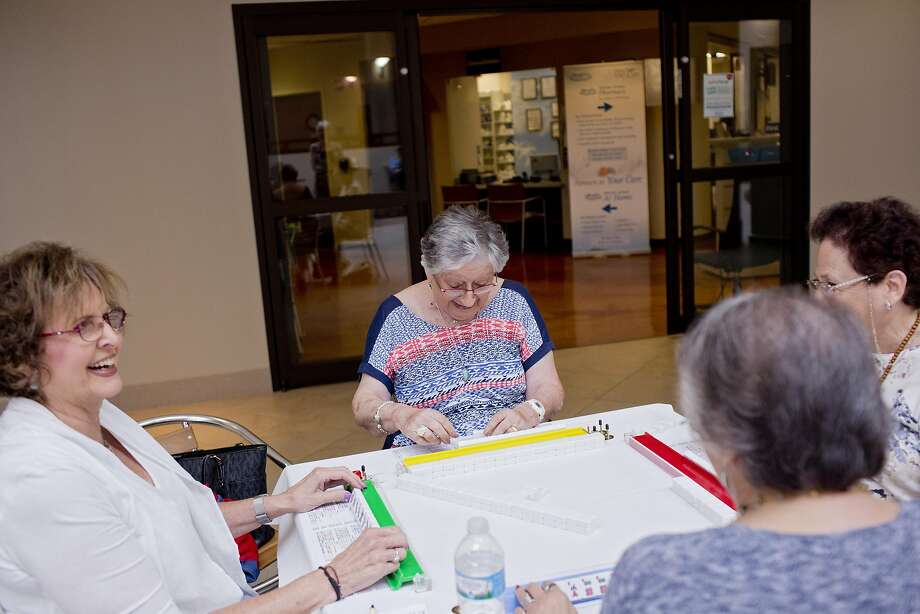 Area residents, including Gwen Taffel (center) and Esther Radin (left), play mah-jongg at Henry Ford West Bloomfield Hospital in Michigan. Photo: LAURA MCDERMOTT, NYT
