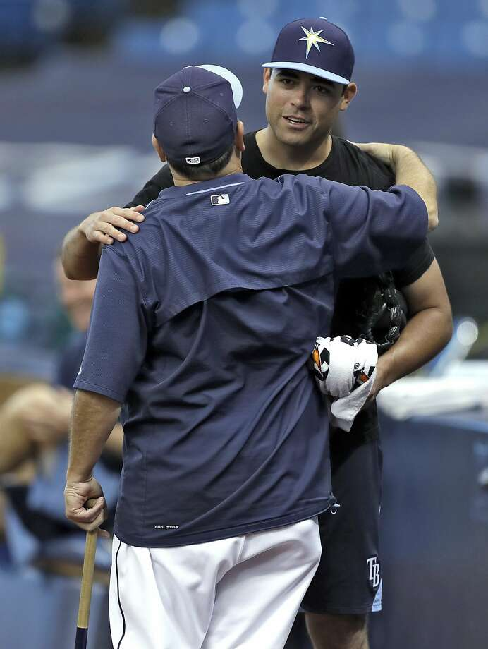 "Matt Moore, right, hugs video coordinator Chris ""Chico"" Fernandez after being traded by Tampa Bay to the Giants on Monday. Photo: Chris O'Meara, Associated Press"