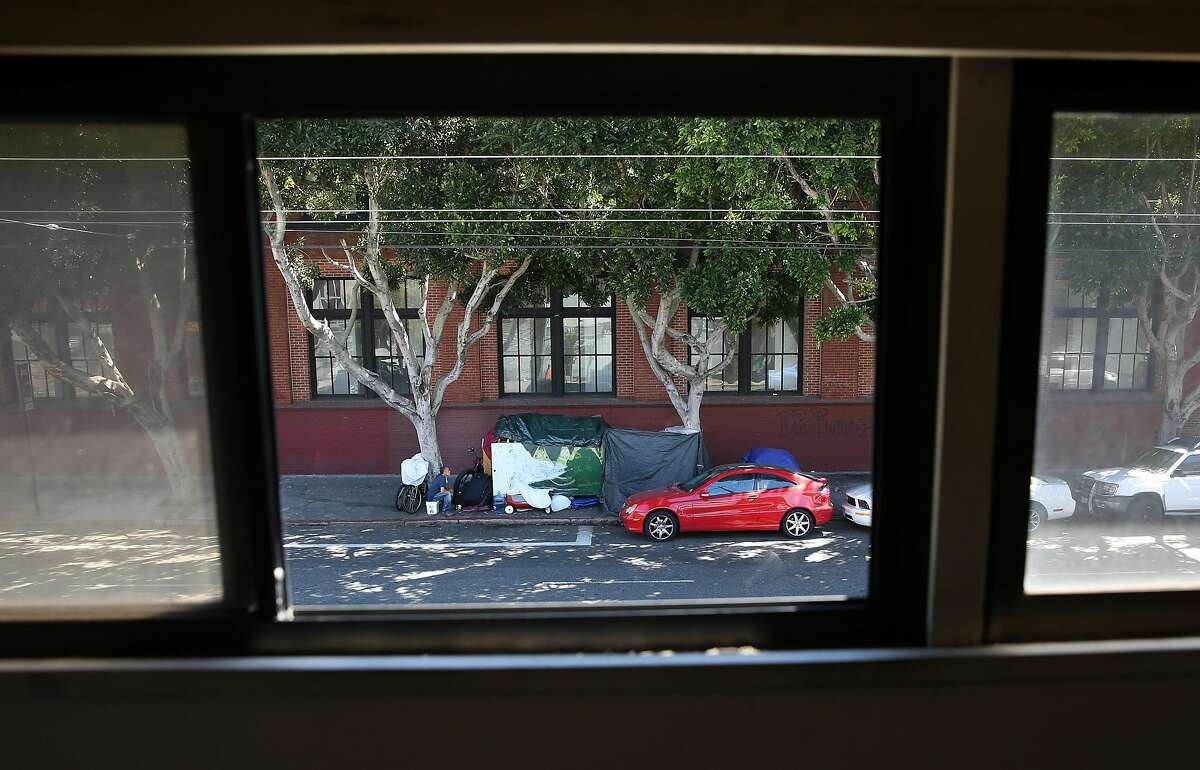 A homeless encampment seen through the windows of building owner Doug MacNeil of Spiral Binding, on Monday, August 1, 2016, in San Francisco, Calif.