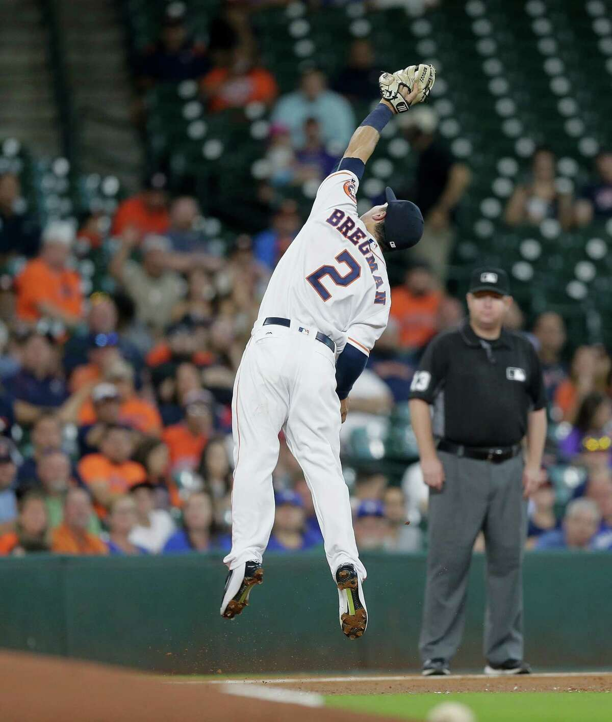 HOUSTON, TX - AUGUST 01: Alex Bregman #2 of the Houston Astros makes a catch on a high chop to retire Darwin Barney #18 of the Toronto Blue Jays in the third inning at Minute Maid Park on August 1, 2016 in Houston, Texas.