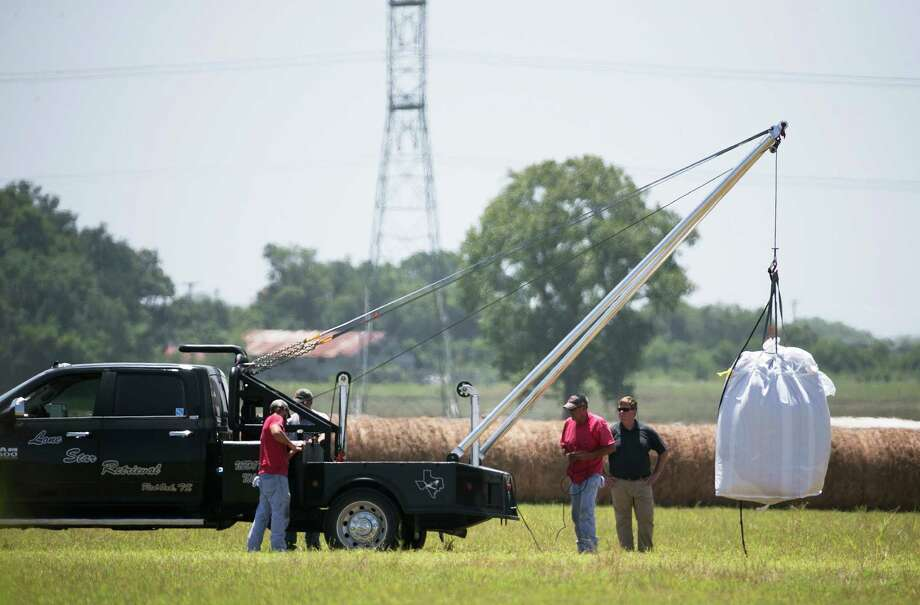 A crew hoists a bag holding the remains of a hot air balloon that crashed Saturday onto a waiting truck at the scene near Lockhart, Texas, Monday, Aug. 1, 2016. Sixteen people were killed in the incident. (Deborah Cannon/Austin American-Statesman via AP) Photo: Deborah Cannon, Associated Press / Austin American-Statesman
