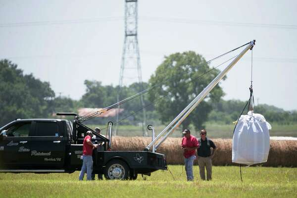 A crew hoists a bag holding the remains of a hot air balloon that crashed Saturday onto a waiting truck at the scene near Lockhart, Texas, Monday, Aug. 1, 2016. Sixteen people were killed in the incident. (Deborah Cannon/Austin American-Statesman via AP)