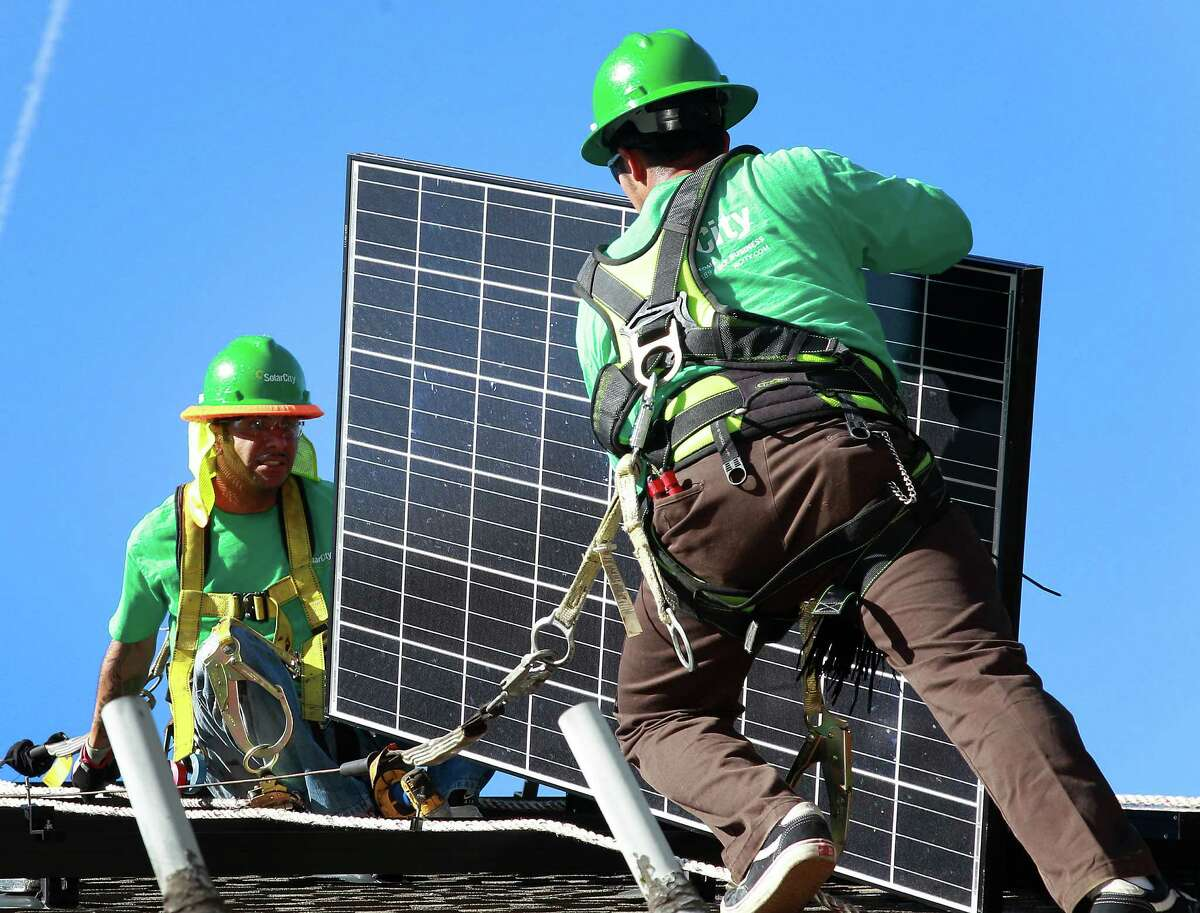 Installers for SolarCity put panels in place in Palo Alto, Calif. Two cousins of Elon Musk lead SolarCity.