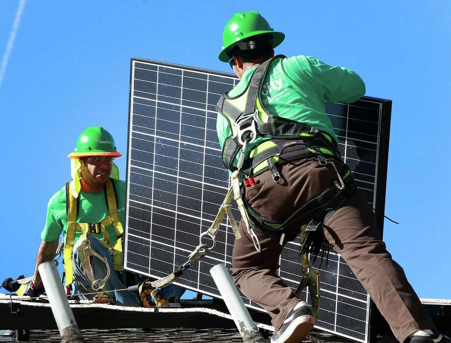 Installers for SolarCity put panels in place in Palo Alto, Calif. Two cousins of Elon Musk lead SolarCity. Photo: Christian Science Monitor, Contributor / ONLINE_CHECK