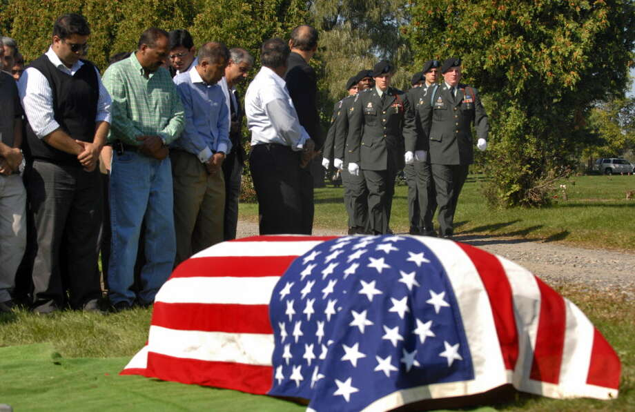 An honor guard from the 10th Mountain Division of Fort Drum approaches  the casket of 1st Lt. Mohsin Naqvi, killed in Afghanistan by a roadside bomb on September 17, 2008, during his burial service on Monday, Sept. 22, 2008, in Colonie, N.Y.  (Philip Kamrass/Times Union archive) Photo: PHILIP KAMRASS / 00000417B