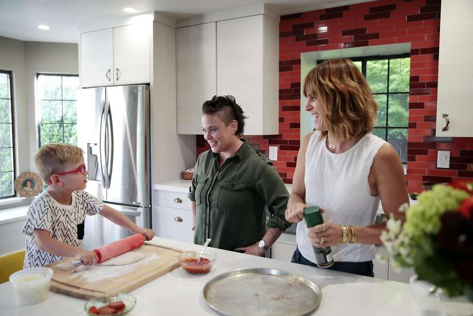 Katie Evans-Reber (center) and her wife, Amy Evans-Reber, make pizza with their 4-year-old son, Cash. Photo: RAMIN RAHIMIAN, Special To The Chronicle