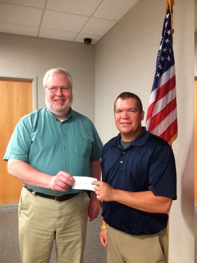 Kevin Barnum, treasurer for Midland County Search and Rescue, accepted a check for more than $1,900 from Scott Billingsley.