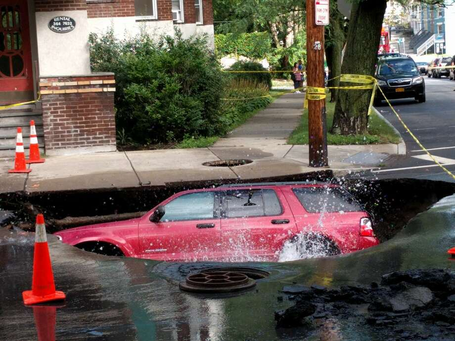 A sinkhole on Albany's Elberon Place slowly consumes Steeve Pierre's 2005 Ford Escape. The Albany Medical College student was relying on anti-stress skills he learned in medical school to deal with the loss of his car. (J.p. Lawrence / Times Union)