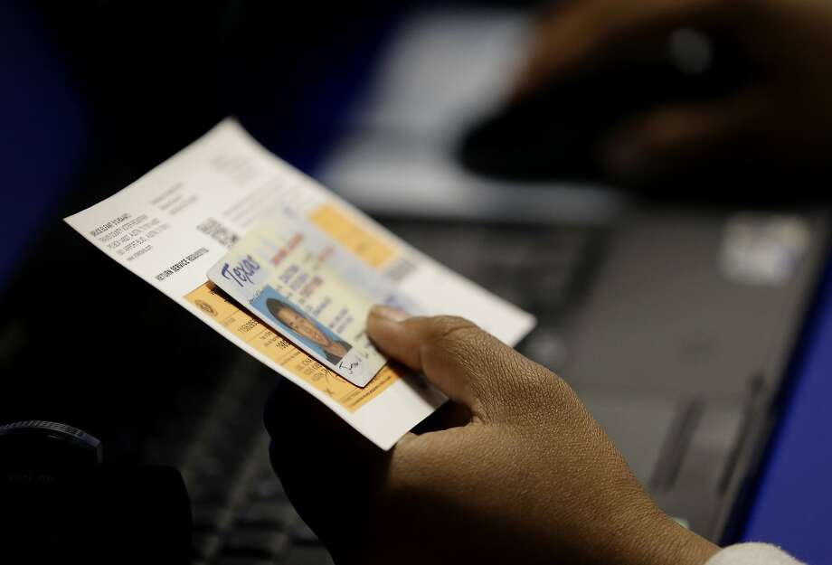 An official checks an Austin, Texas, voter's identification at an early voting polling site in 2014. A U.S. court ruled the state's voter ID law discriminatory. Photo: Eric Gay, Associated Press