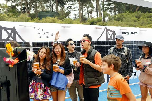 IMAGE DISTRIBUTED FOR NRG - Festivalgoers at Outside Lands Music Festival take a picture in front of a full-scale solar panel provided by festival sponsors NRG in San Francisco, Saturday, Aug. 8, 2015.  Festival attendees can relax inside of the NRG EcoLounge, equipped with NRG Street Charge solar-powered charging stations, a live feed of the main stage and a balcony featuring an EVgo charging unit and views of the Twin Peaks and Panhandle stages.  (Photo by Alison Yin/AP Images for NRG)