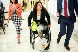 Rep. Tammy Duckworth, D-Ill., listens to a staffer while going to a meeting on Capitol Hill on July 7. MUST CREDIT: Melina Mara, The Washington Post.