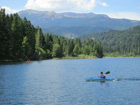 A kayaker paddles across Lake Siskyou with 9,025-foot Mount Eddy providing a backdrop. A 10-mph speed limit at Lake Siskiyou keeps the lake quiet for paddlers and swimmers, and the lake is near full as the camping season hits it crown for summer. Photo: Tom Stienstra / The Chronicle