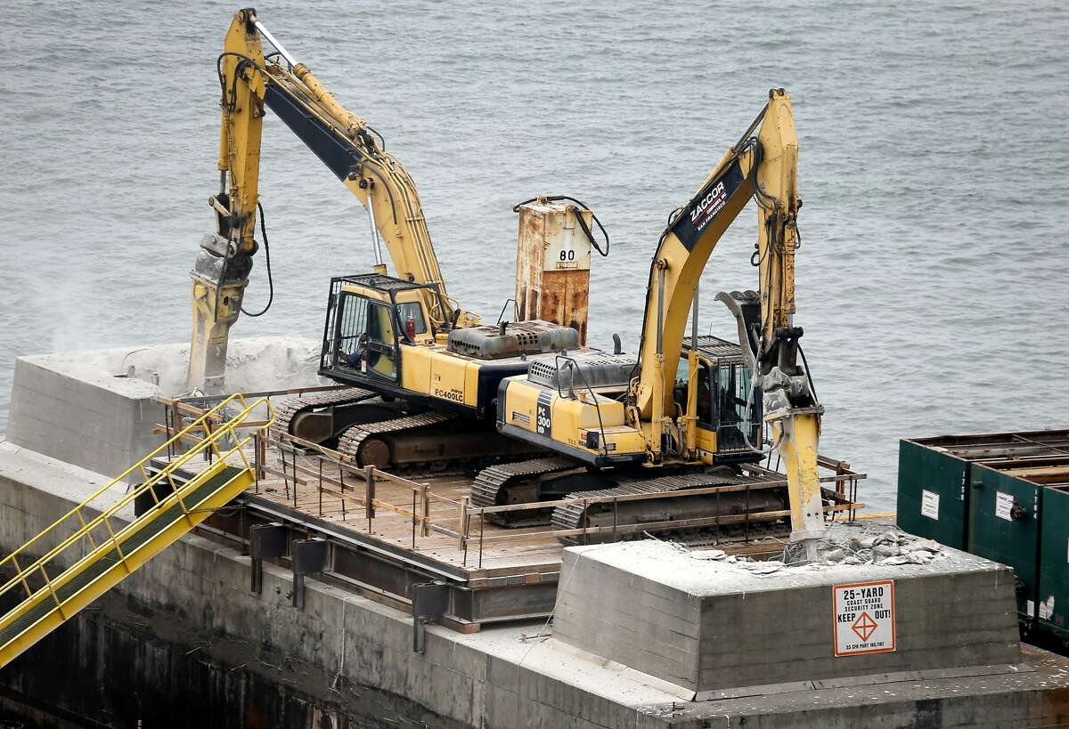 Heavy equipment hammers against the concrete foundation of a pier from the old eastern Bay Bridge as demolition work continues in Oakland, Calif. on Tuesday, Aug. 2, 2016.