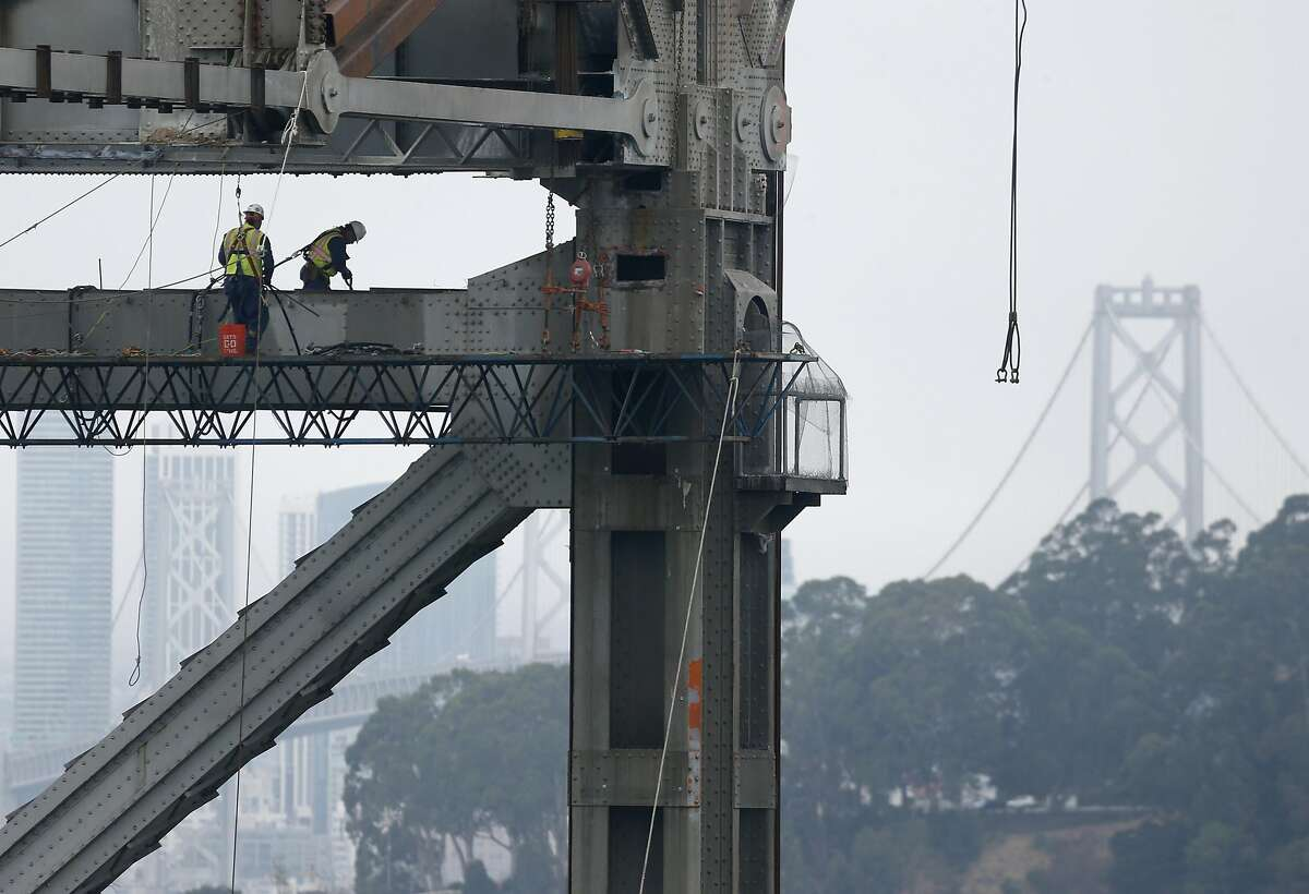 Workers prepare a section of the old eastern Bay Bridge for demolition in Oakland, Calif. on Tuesday, Aug. 2, 2016.